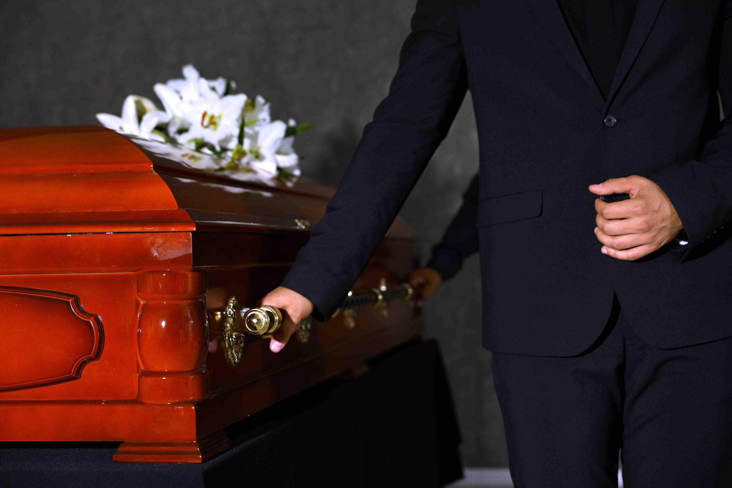 Young woman with red rose near casket in funeral home, closeup